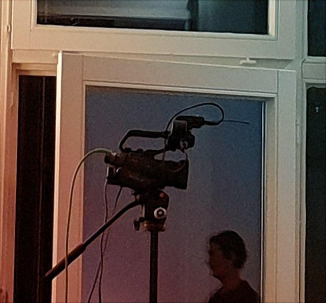 In einer Glastür spiegelt sich eine Videokamera und der Kopfumriss einer Vortragenden