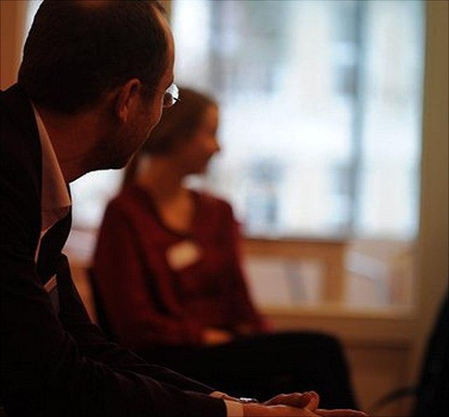 Gesprächssituation mit einem Unternehmensvertreter und einer Studentin, beide sitzend in einem großen Raum