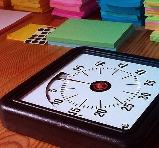 Uhr zum Zeitnehmen liegt auf einem Tisch vor mehreren Stapeln bunter Moderationskarten