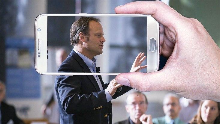 Ein Mann trägt in einem Raum vor Menschen vor und wird dabei mit dem Handy gefilmt.