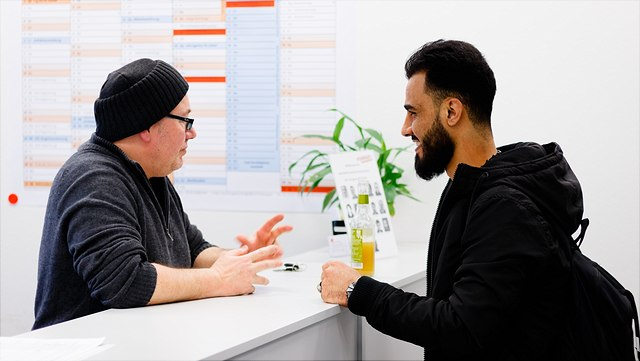 Beratungssituation - zwei Personen stehen an Counter, sprechen miteinander.