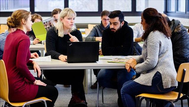 Situation im Klassenraum. Fünf Personen am Gruppentisch, eine Person mit Laptop, erklärt etwas.