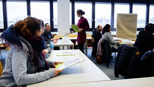 Situation im Klassenraum. Eine Person verteilt Material an sitzende Personen.
