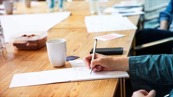 Tisch mit Kaffeetasse, Kuchenschale und schreibender Hand auf einem Block