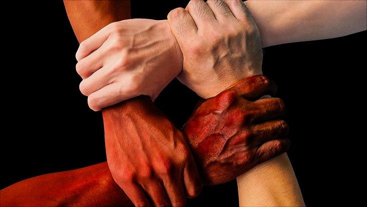 Vier Hände die einander halten.