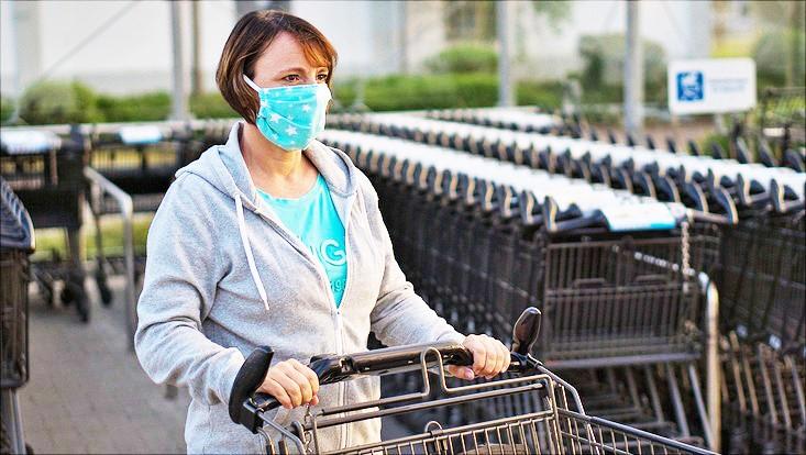 Frau mit Einkaufswagen und Mund-Nasen-Schutz