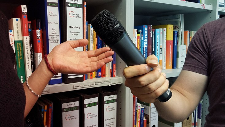 Interviewsituation: Hand des Interviewers mit Mikrofon und gestikulierende Hand der Interviewten