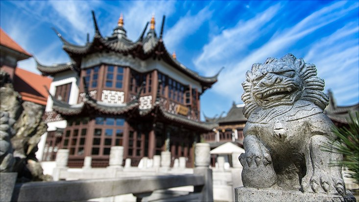 stone lion guarding a two-story chinese tea house with bright sky in the background