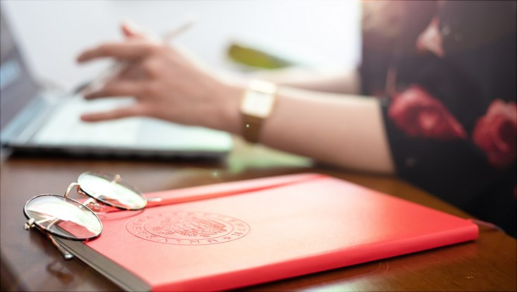 glasses lying on red notebook reflecting the bright sun while woman working on laptop in the background