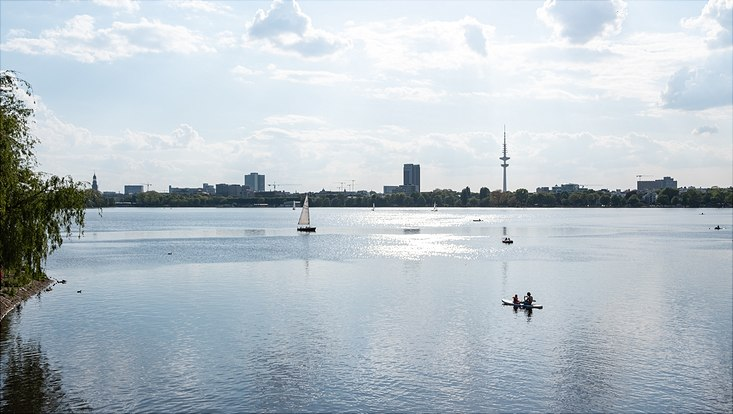 sunny panorama view over Alster lake and tv tower, on the water sailing boats and canoes