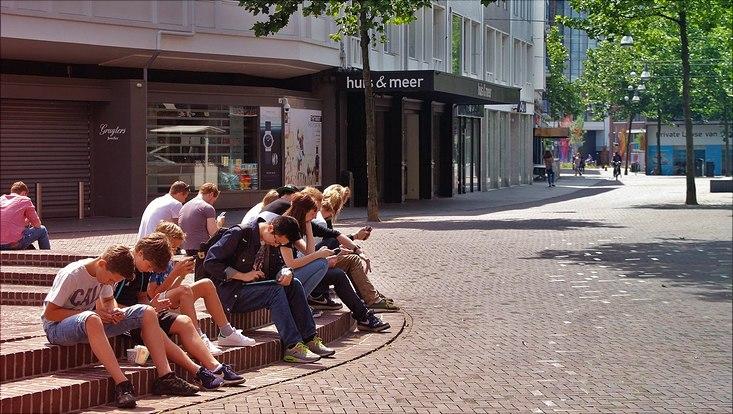 Jugendliche mit Smartphones in einer Fußgängerzone