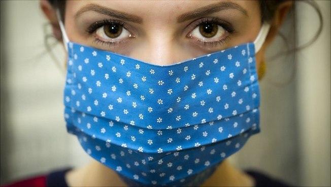 Eine Frau mit Mund-Nasen-Bedeckung