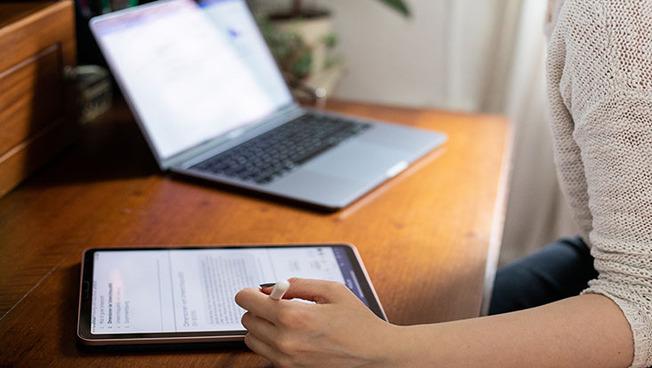 Person am Schreibtisch. Bildschirm und Tablet.