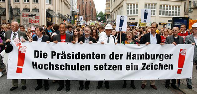 """Vertreterinnen und Vertreter der Hamburger Hochschulleitungen bei der Sternmarsch-Demo tragen ein Banner mit der Aufschrift: """"Die Präsidenten der Hamburger Hochschulen setzen ein Zeichen."""""""