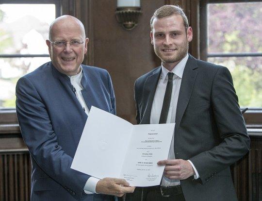 Der Preisträger Christian Folde erhält eine Auszeichnung für seine Magisterarbeit