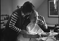 Woman feeds an elderly man