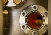 Eine Wolke ultrakalter Atome leuchtet in einer Vakuumkammer