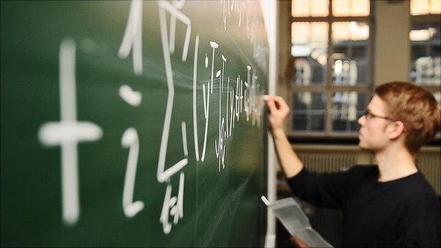 Schüler schreibt eine Formel an die Tafel