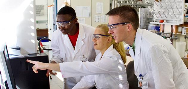 Drei Nachwuchswissenschaftler in einem Labor diskutieren Werte am PC.