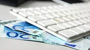 Geldscheine unter eine Tastatur geklemmt