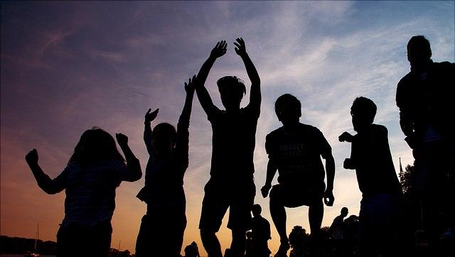 Schattenrisse von in die Luft springenden jungen Männern