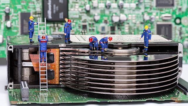 Minaturfiguren arbeiten an Computerteilen