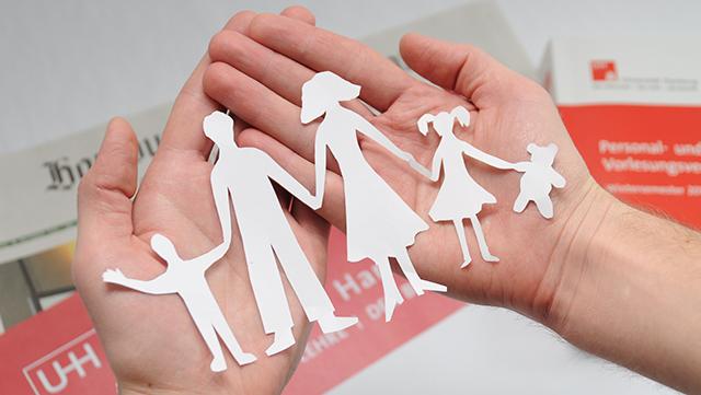 Hände halten aus Papier ausgeschnittene Familie
