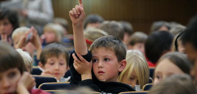 Kleiner Junge meldet sich im Hörsaal