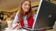 Studierende mit einem Laptop in einem Café