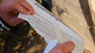Studierende zerreißt ein Blatt Papier
