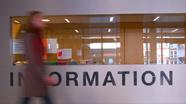 Studierende geht an Informationsstand vorbei