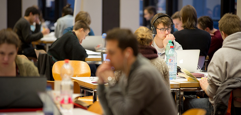 Studierende an Schreibtischen während Langen Nacht der aufgeschobenen Hausarbeiten in der Staats- und Universitätsbibliothek.