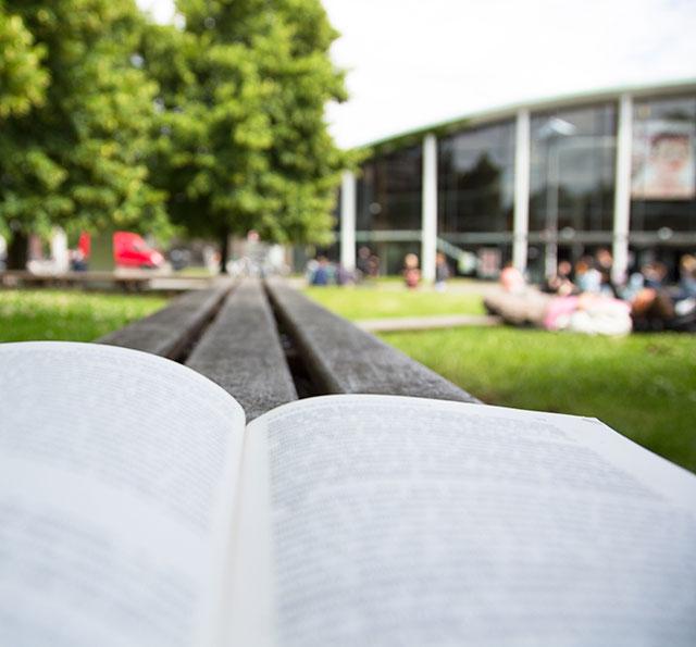 Aufgeschlagenes Buch auf dem Campus, im Hintergrund das Audimax