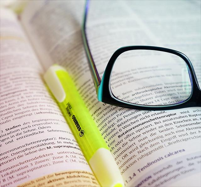 Brille und Marker auf einem aufgeschlagenen Buch