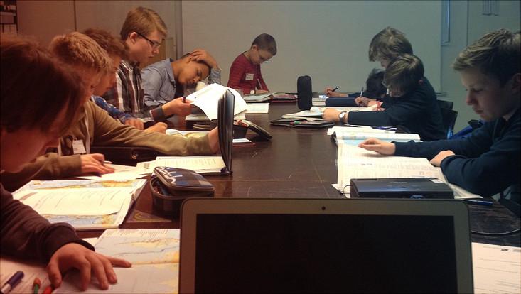 Jungen sitzen am Tisch und arbeiten in Büchern