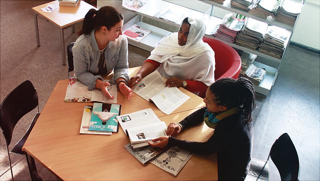 Drei Studentinnen sitzen an einem Tisch. Sie haben unterschiedliche Hautfarben, eine von ihnen trägt Kopftuch.