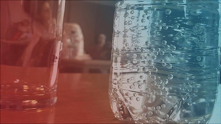 Im Vordergrund steht eine Wasserflasche auf dem Tisch, im Hintergrund steht eine Frau vor einer Tafel