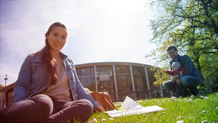 Studierende auf dem Campus, im Hintergrund ihr Freund mit dem Kind