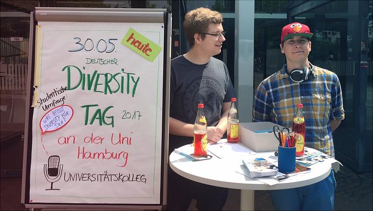 Zwei Mitarbeiter des Universitätskollegs an ihrem Stand vor dem Audimax