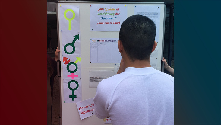 Ein Student betrachtet das Plakat zur gendergerechten Sprache in Hausarbeiten