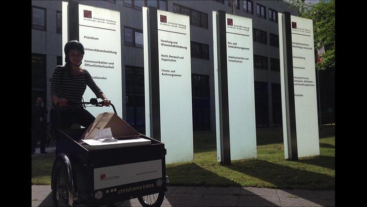Eine Mitarbeiterin der Stabsstelle Gleichstellung transportiert Infomaterialien für den Diversity-Tag mit einem Lastenfahrrad.