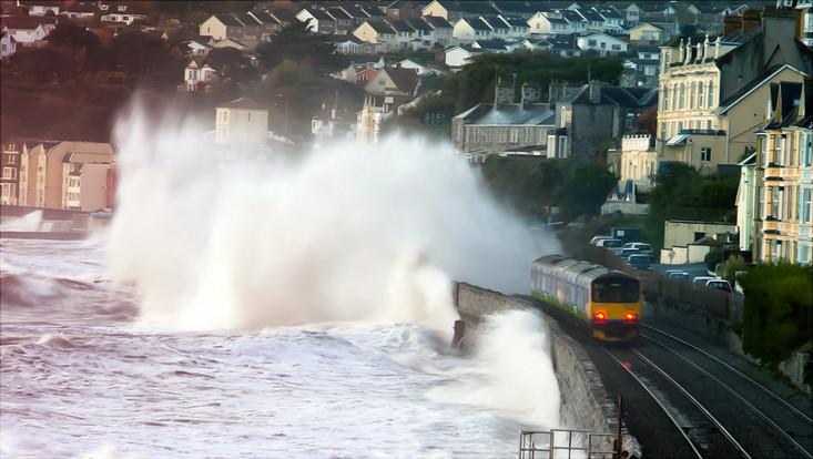 Bahn fährt an Küstenstrecke durch Welle