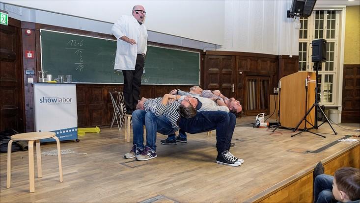 Vier Männer haben sich hockend so aufeinander abgestützt, dass sie sich ohne Stuhl gegenseitig in der Hocke tragen