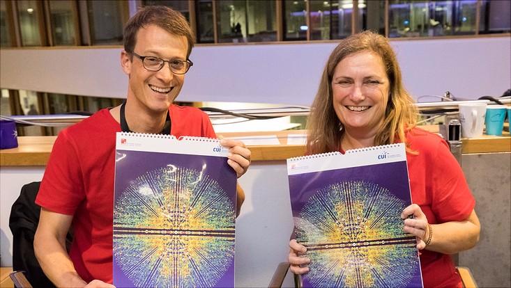 Kollegen vom CUI-Team präsentieren einen Kalender mit Forschungsbildern