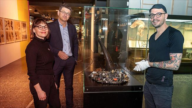 Die Kuratoren Anna-Sophie Springer und Etienne Turpin zusammen mit Matthias Glaubrecht an einem Kunstwerk der Ausstellung: einer Rhinozeroshorn-Replik von Mark Dion, umgeben von Flohmarktgegenständen.