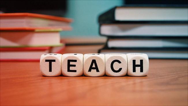 """Würfel, die das Wort """"teach"""" bilden"""