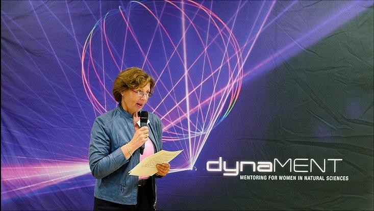 Links im Bild ist die aktuelle Gleichstellungsbeauftragte der Universität Hamburg, Frau Paschke-Kartzin zu sehen, die ein Mikrofon in der linken Hand hält und anscheinend gerade eine Ansprache hält. Sie steht vor einer Wand mit dem dynaMENT-Logo.