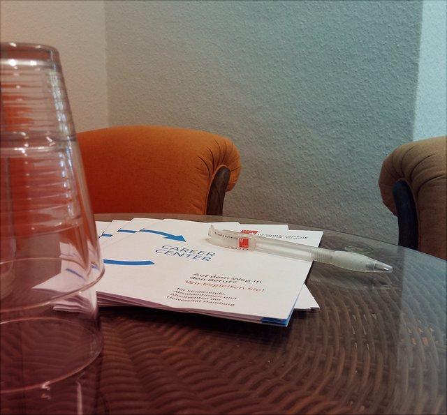 Gläser und Hefte auf einem Tisch vor einem Sofa und einem Sessel