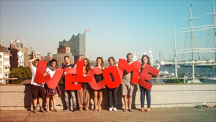 """Menschen vor Hamburger Skyline halten Buchstaben """"Welcome"""" hoch."""