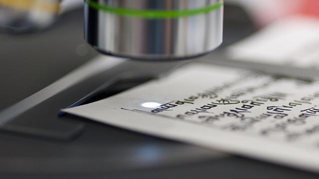 Mikroskop untersucht ein altes Pergament